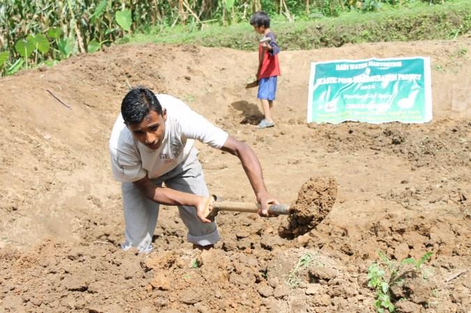 Village boy digging the pond